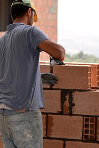 Maçon construit murs en brique