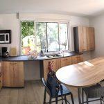 extension maison à Parcieux : cuisine finalisée avec teintes claires au mur, et meubles en bois