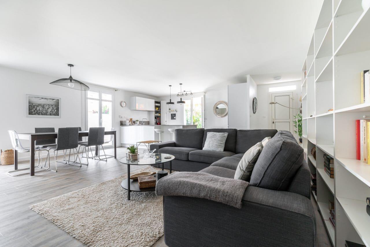 rénovation extension maison salon canapé cuisine aménagée équipée meuble laqué blanc luminaire table à manger entrée Pomérols